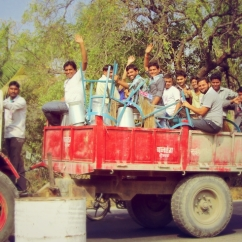 A truck containing joyful Indian men.