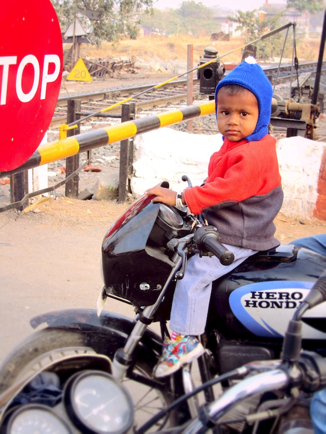 A boy on top of a motorcycle.