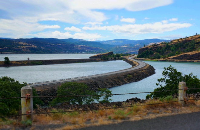 The road subtly zigzags in the Columbia River, from the Washington side.